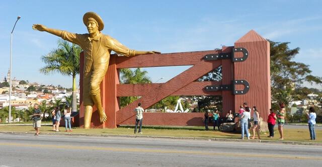 """Turistas param na estrada para tirar fotos com o """"menino da porteira"""". Foto: Reprodução Guia de Ouro Fino"""