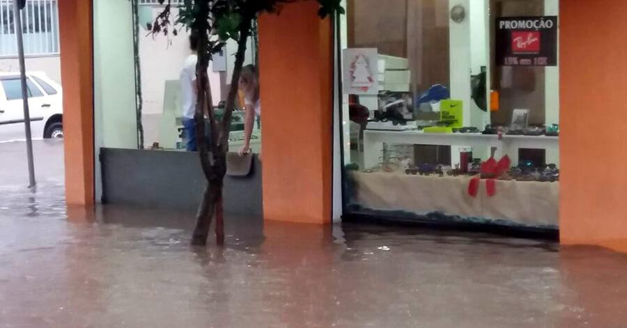 Comerciante tenta proteger loja de ser alagada pela chuva.