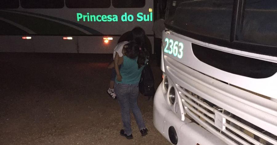 Mãe com filha no colo esperando após ônibus quebrar a noite no Bairro Pantano.